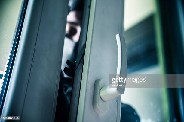 burglar breaks into a residential building - burglar stock pictures, royalty-free photos & images