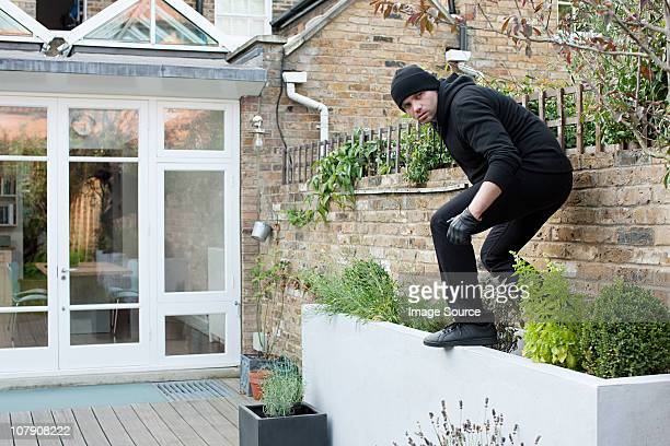 burglar climbing on wall - burglar stock pictures, royalty-free photos & images