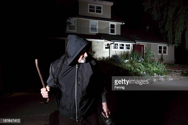 Burglar contemplating breaking-in to a home.