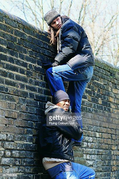 Burglar Helping Another Man Climb a Wall