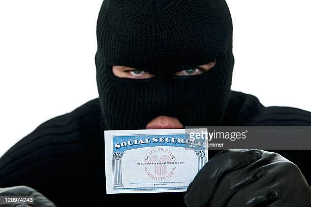 Cambrioleur tenant une carte de sécurité sociale pour le vol d'identité