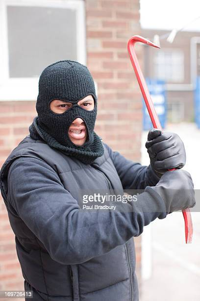 burglar in ski mask wielding crowbar - balaclava stock pictures, royalty-free photos & images