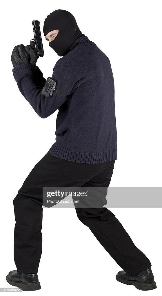 Burglar in ski mask with handgun : Stock Photo