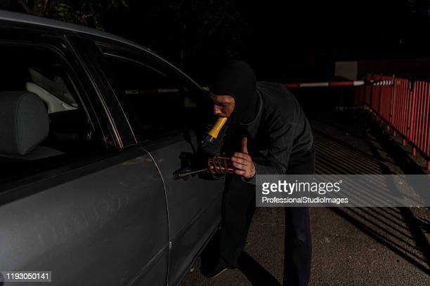 a burglar is stealing the car in the night hours - looting stock pictures, royalty-free photos & images