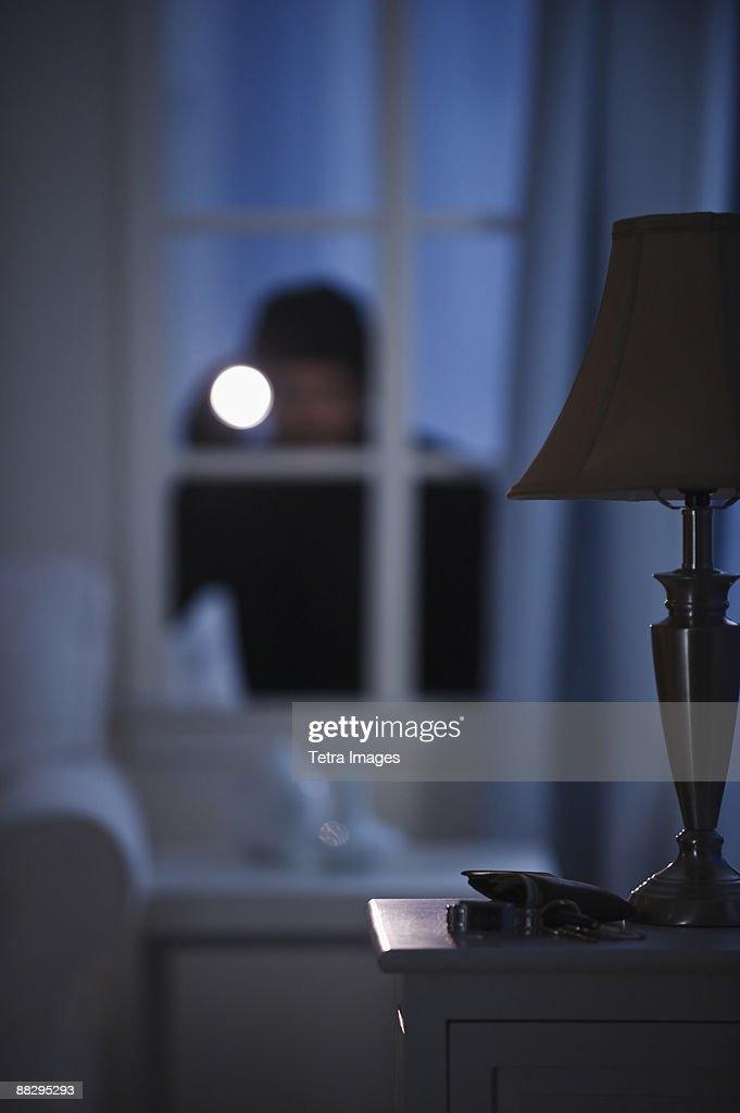 Burglar looking in house window : Stock Photo