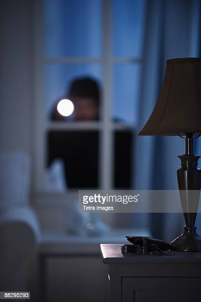 burglar looking in house window - burglar stock pictures, royalty-free photos & images
