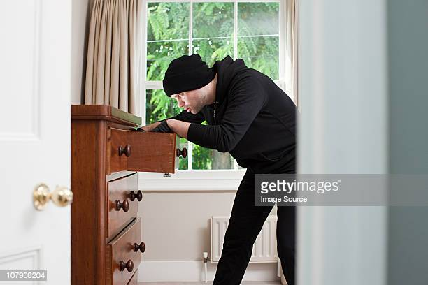 Burglar opening drawer and looking inside