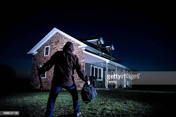 burglar outside a house at night - burglar stock pictures, royalty-free photos & images