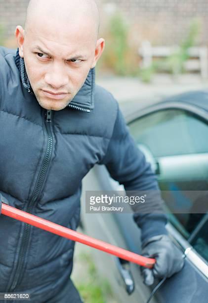 Burglar prying car window open with crowbar