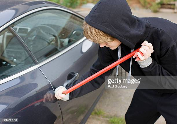 burglar prying car window open with crowbar - burglar stock pictures, royalty-free photos & images