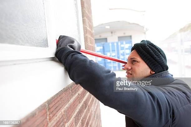 Einbrecher prying Fenster geöffnet mit Brecheisen