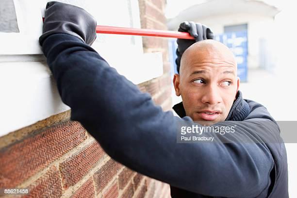 Burglar prying window open with crowbar