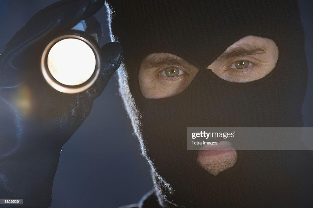 Burglar shining flashlight : Stock Photo