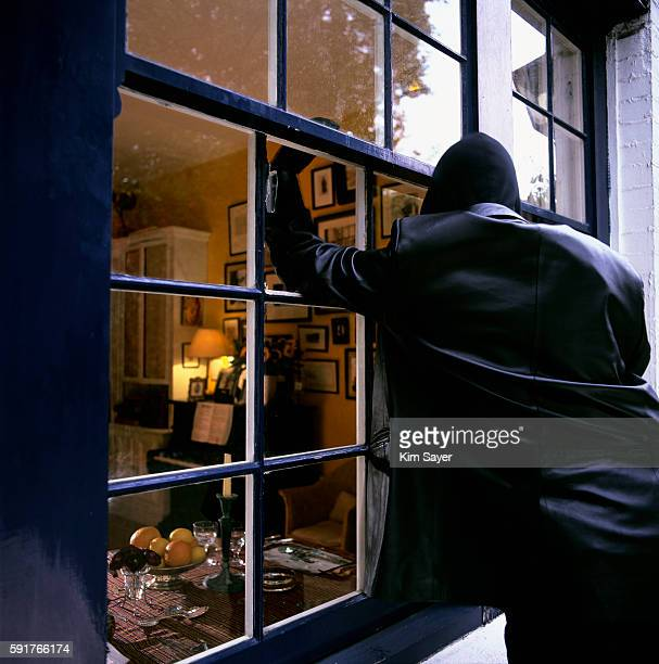 burglar smashing through window - burglar stock pictures, royalty-free photos & images