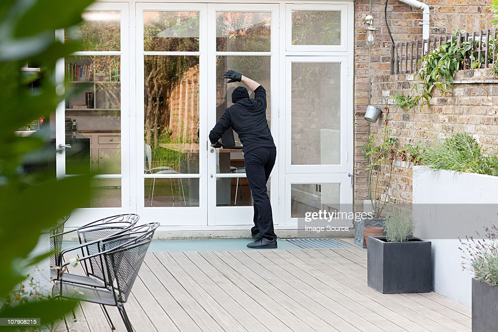 Burglar standing at patio door : Stock Photo