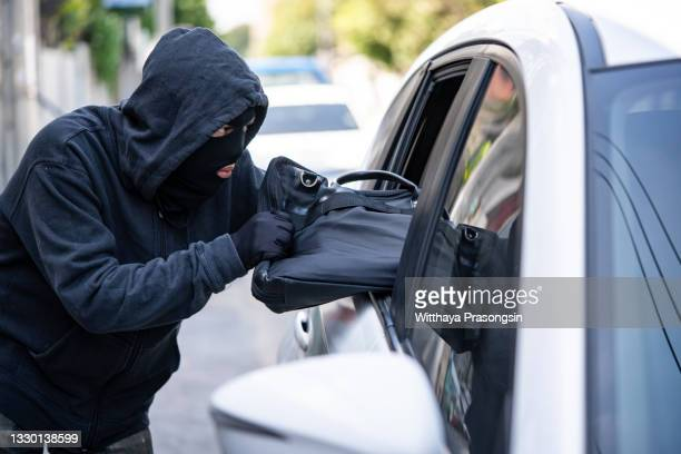 burglar steal a shoulder bag through the window of car - hooded top stock pictures, royalty-free photos & images