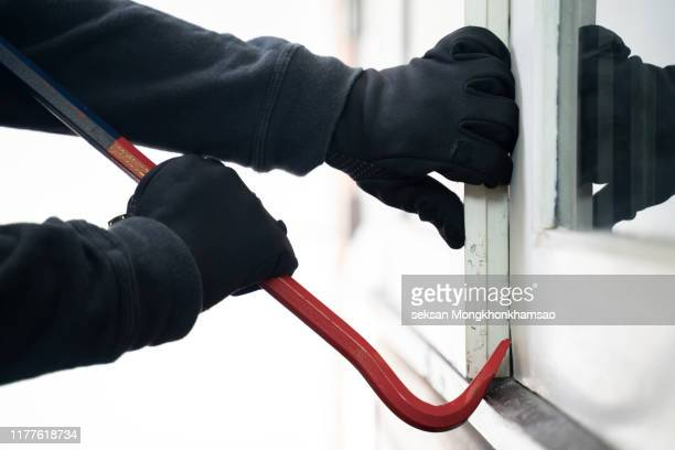 burglar trying to break into a house with a crowbar - burglar stock pictures, royalty-free photos & images