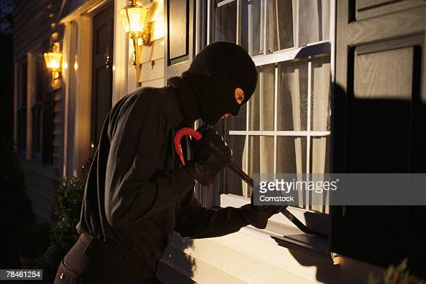 Burglar trying to pry open window on house