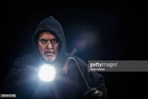 Burglar wearing a dark hoodie with crowbar and flashlight