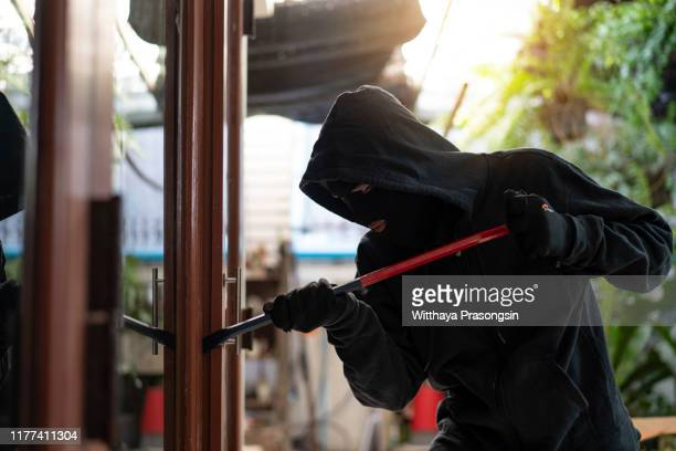 burglar wearing black clothes and leather coat breaking in a house - burglar stock pictures, royalty-free photos & images