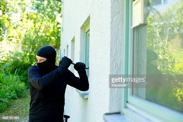 Burglar with crowbar breaking window