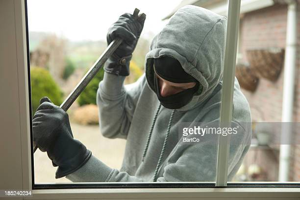 burglar with crowbar trying to enter house, stealing valuables - burglar stock pictures, royalty-free photos & images