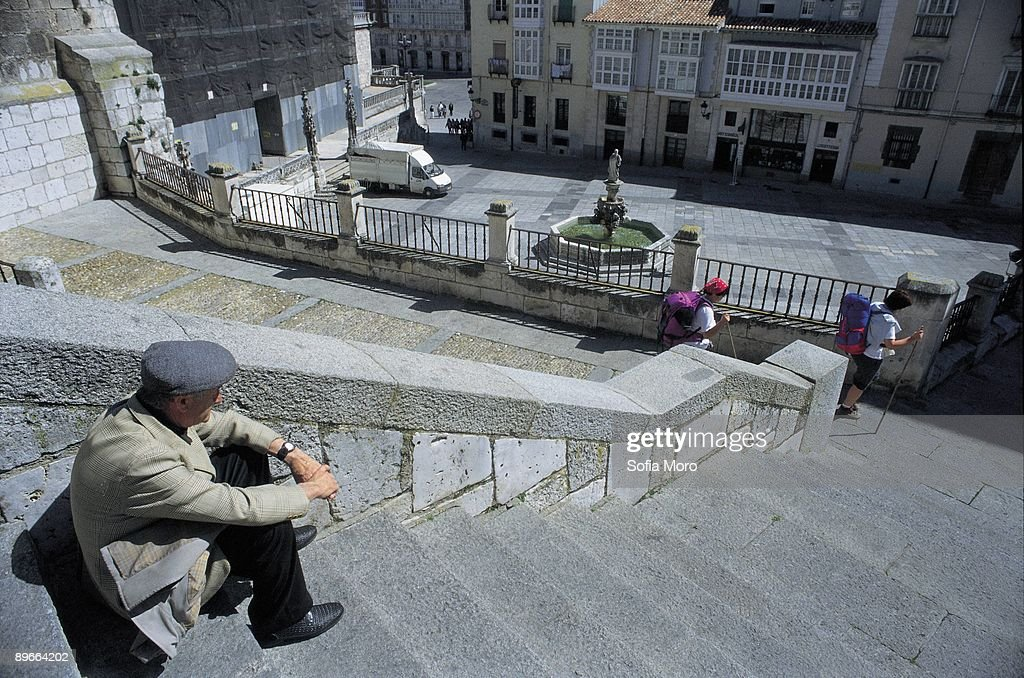 Burgos A man sat down in the stairways of the environment of the Cathedral observes two tourists loaded with rucksacks : News Photo