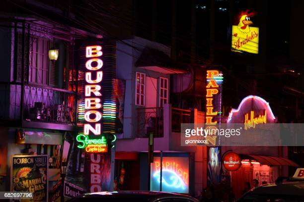 burgos street neon lights by night, manila, philippines - makati stock photos and pictures