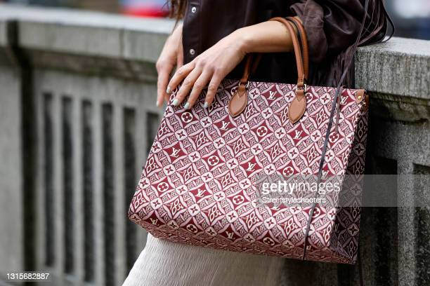 Burgundy and white bag with monogram logo pattern by Louis Vuitton as a detail of German singer Jasmin Wagner during a street style shooting on May...