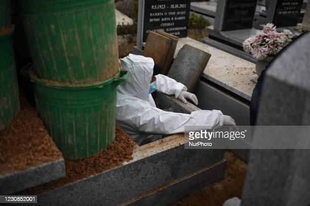 Burial services employee of 'Chevra Kadisha', standing inside a grave, waiting to receivec the body of Romanian born Holocaust Survivor Golda...