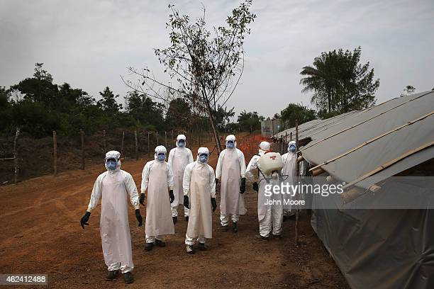 A burial team awaits decontamination at the USbuilt cemetery for 'safe burials' on January 27 2015 in Disco Hill Liberia The cemetery operated by...