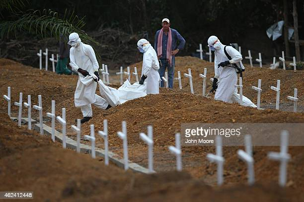 """Burial team carries the body of a one-year-old to be interred at the U.S.-built cemetery for """"safe burials"""", as American Ebola response coordinator..."""