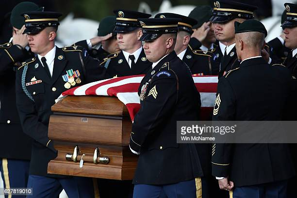 A burial team carries the casket of US Army Staff Sgt Kevin J McEnroe during the soldier's burial service at Arlington National Cemetery December 5...