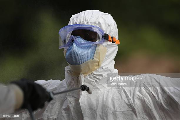 A burial team member wearing personal protective equipment stands for decontamination spray at the USbuilt cemetery for safe burials on January 27...