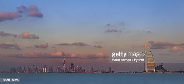 Burj Al Arab Hotel In Front Of River Against Sky At Dusk In City