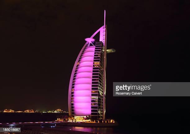 Burj Al Arab Hotel with bright pink floodlighting.