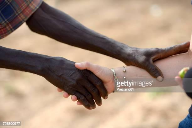 Burkina Faso, old African man shaking hands with white woman