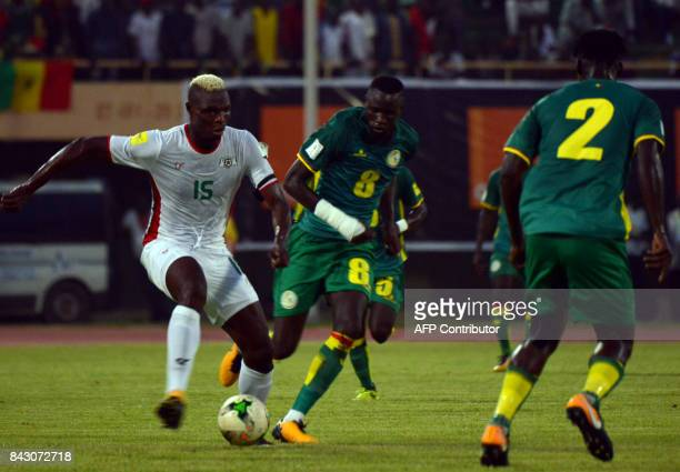 Burkina Faso's Aristide Bance vies with Senegal's Cheikhou Kouyate and Kara Mbodji on September 5 2017 at the stade du 26 aout in Ouagadougou during...