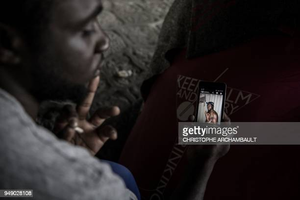 TOPSHOT Burkina Faso's Aziz Porogo a 28yearold migrant shows a picture of himself taken in Libya as he sits by his tent at a makeshift camp set under...