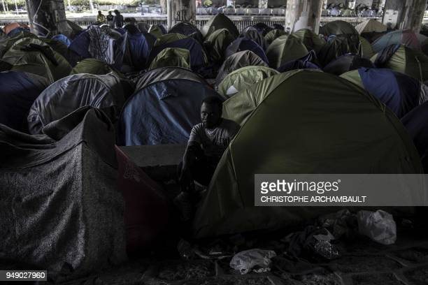 Burkina Faso's Aziz Porogo a 28yearold migrant sits in his tent at a makeshift camp set under a bridge near Porte de la Villette northern Paris on...