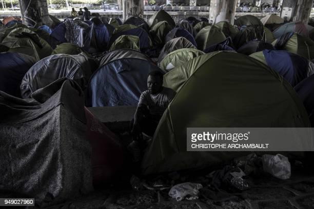 Burkina Faso's Aziz Porogo a 28yearold migrant sits in his tent at a makeshift camp set under a bridge near Porte de la Villette northern Paris on...