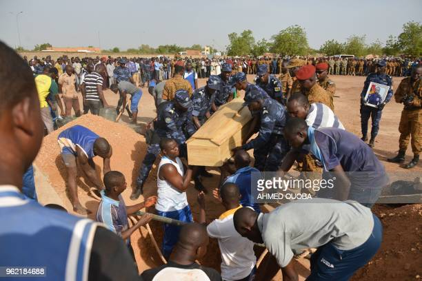 Burkina Faso's Gendarmes carry their colleague's coffin during the funeral ceremony on May 24 2018 in Ouagadougou following an operation to capture...