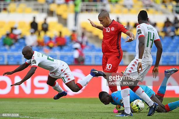Burkina Faso's goalkeeper Herve Kouakou Koffi catches the ball to block a shot on goal by Tunisia's midfielder Wahbi Khazri next to Burkina Faso's...
