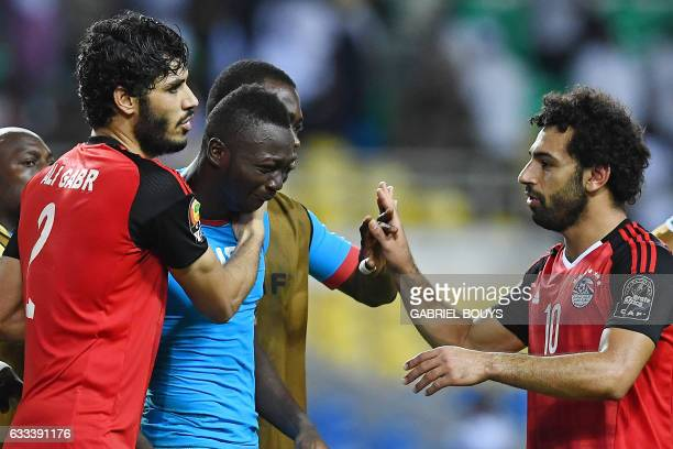 TOPSHOT Burkina Faso's goalkeeper Herve Kouakou Koffi is consoled by Egypt's defender Ali Gabr and Egypt's forward Mohamed Salah as he cries at the...