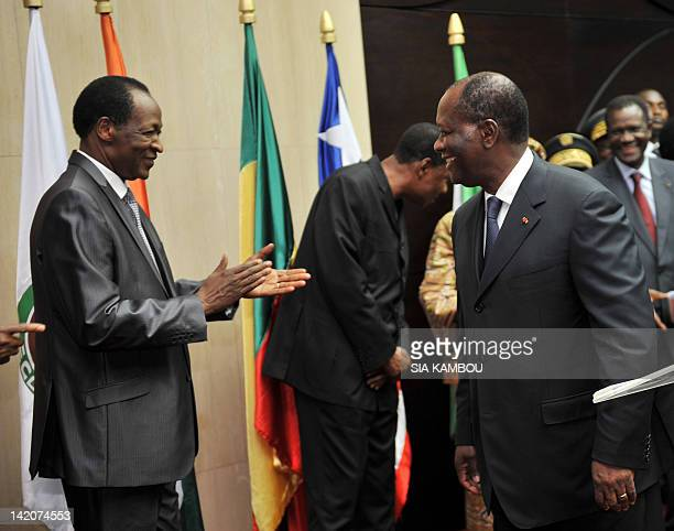 Burkina Faso's President Blaise Compaore applauds Alassane Ouattara Ivory Coast's president and Leader of the ECOWAS west African bloc during a...