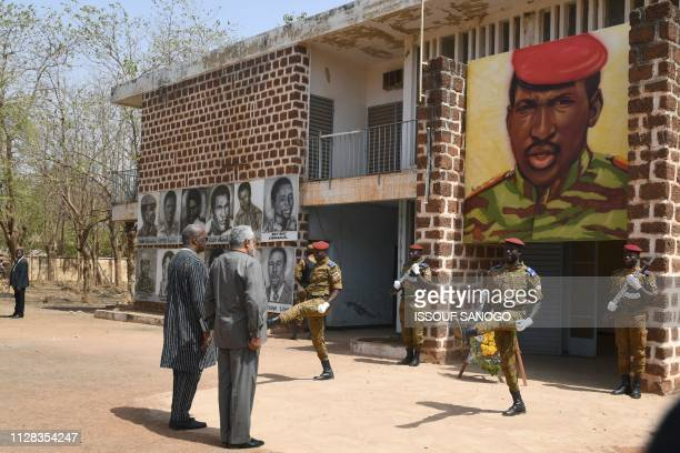 Burkina Faso's President Roch Marc Christian Kabore and Ghana's former President Jerry Rawlings stand on March 2 2019 under the portrait of Burkina...