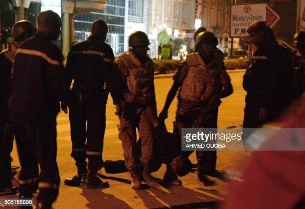 TOPSHOT Burkina Faso's soldiers carry the body of a man in the surroundings of the Splendid hotel during an attack on both the hotel and a restaurant...