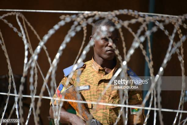 Burkinabe man patrols the army's headquarters in Ouagadougou on March 3, 2018 a day after dozens of people were killed in twin attacks on the French...