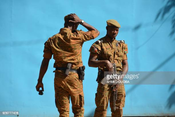Burkinabe men patrol the army's headquarters from the roof in Ouagadougou on March 3, 2018 a day after dozens of people were killed in twin attacks...