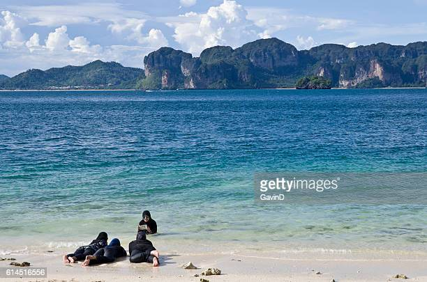 burkini wearing muslim women pose for photograph in krabi thailand - muslim woman beach stock photos and pictures